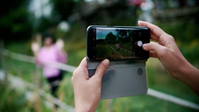 cu : donna che scatta foto a sua madre con lo smartphone - macchina da presa manuale video stock e b–roll