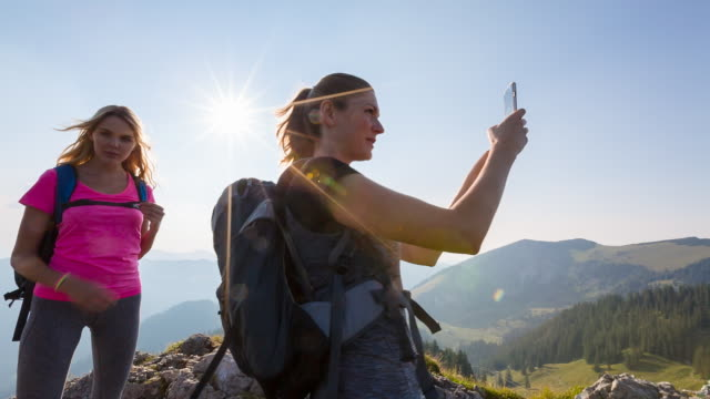 Woman taking photo with mobile phone at mountain summit