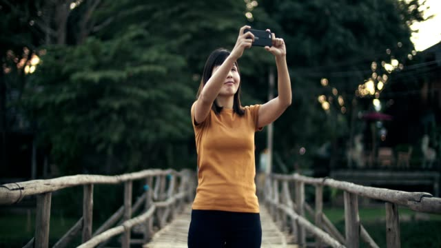 woman taking photo with smart phone on the wooden bridge - mae hong son province stock videos and b-roll footage