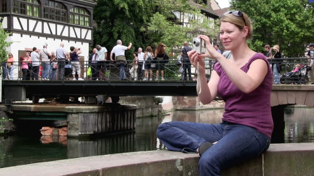 ms woman taking photographs at old town / strasbourg, alsace, france  - 僅年輕女人 個影片檔及 b 捲影像