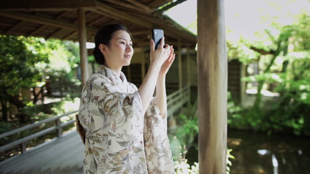 woman taking photographs in peaceful garden - shibamata stock videos & royalty-free footage