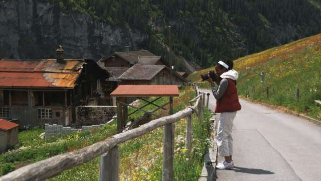 woman taking photographs on an alpine road - gimmelwald stock videos & royalty-free footage