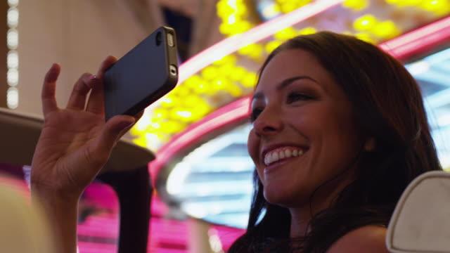 CU Woman taking photographs with smart phone driving through neon illuminated street / Las Vegas,Nevada,USA
