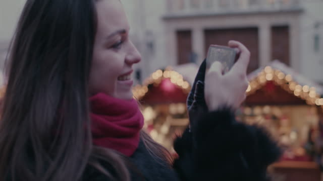 vídeos de stock, filmes e b-roll de woman taking photos and videos with smartphone of lights and stalls at christmas market - celular com câmera