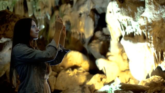 Kvinna att ta foton i en grotta