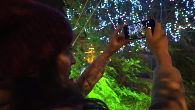 クリスマス ツリーの前で写真を撮る女性。 - 飾り点の映像素材/bロール