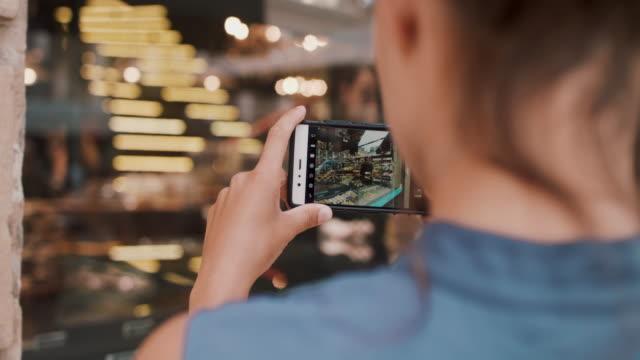 vídeos y material grabado en eventos de stock de woman taking photos of shop - photographing