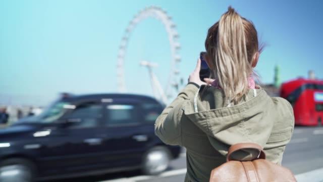 woman taking photos of the london eye - tourist stock videos & royalty-free footage