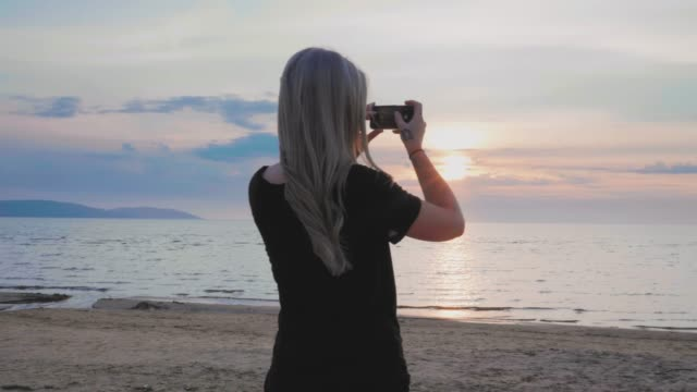 Woman taking photos of the sunset at the beach in Sweden