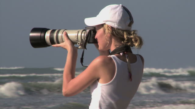 woman taking photos on the beach