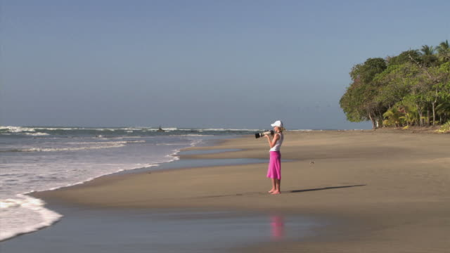 woman taking photos on the beach