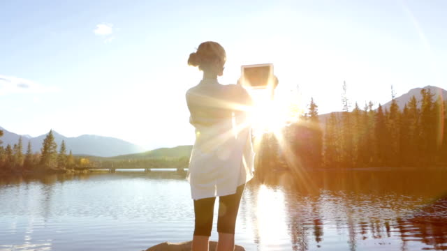 woman taking photos with digital tablet by the lake - jasper national park stock videos & royalty-free footage