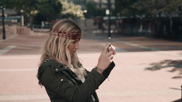 vidéos et rushes de femme prenant une photo dans un cadre urbain - thème de la photographie