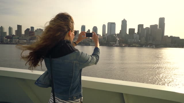 vídeos de stock, filmes e b-roll de woman taking picture of city on the ferry - jaqueta jeans