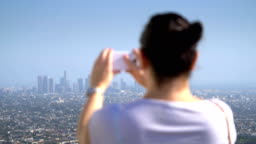 Woman taking picture of downtown in Los Angeles in 4k slow motion 60fps
