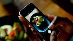 Woman taking picture of food 4k
