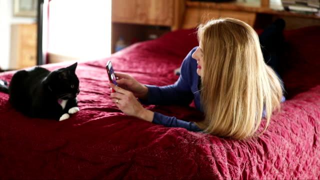 女性は彼女の猫の写真を撮る - photographing点の映像素材/bロール