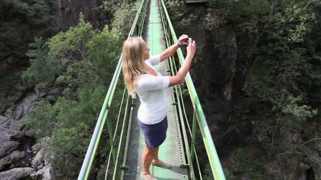 vidéos et rushes de pov of woman taking picture on narrow bridge over gorge - étroit