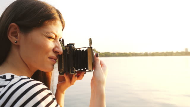Woman taking pictures at sunset using a vintage camera.