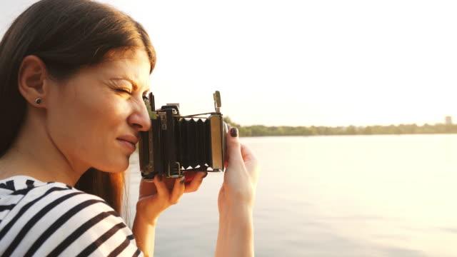 Frau bei Sonnenuntergang mit einem Vintage-Kamera fotografieren.