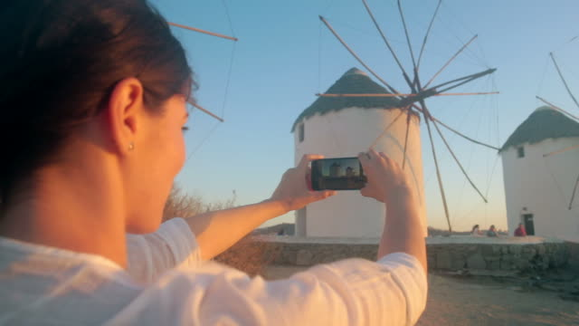 woman taking pictures at windmills in mykonos, greece. - mykonos stock videos and b-roll footage