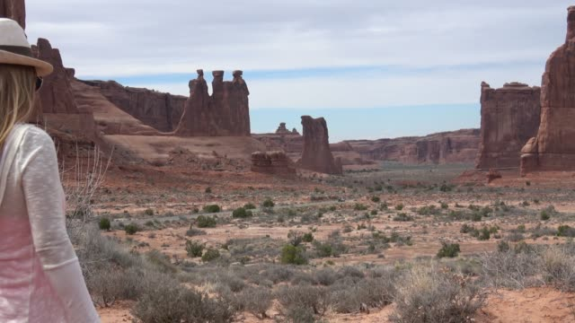 ユタ州アーチーズ国立公園で写真を撮っている女性 - 堆積岩点の映像素材/bロール
