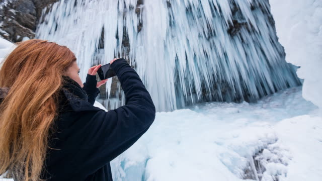 Woman taking pictures of beautiful frozen waterfall
