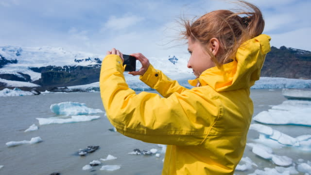 Woman taking pictures of floating icebergs in Jokulsarlon glacier lagoon on a windy day