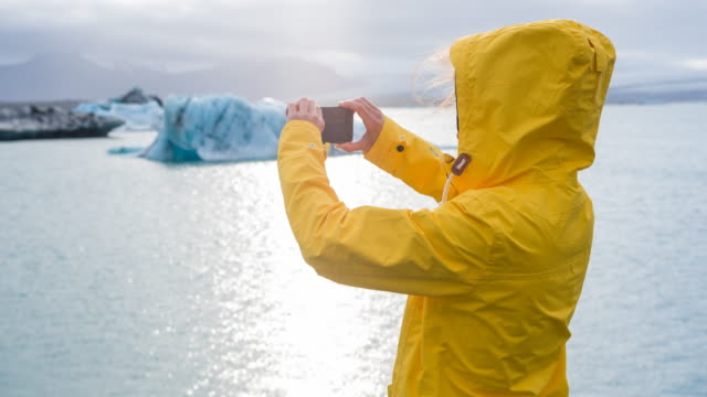 woman taking pictures of icebergs in glacial lake - hood clothing stock videos and b-roll footage