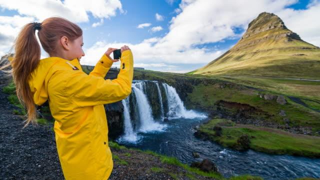 vídeos y material grabado en eventos de stock de mujer de tomar fotografías de la montaña de kirkjufell con smartphone - volcán extinguido
