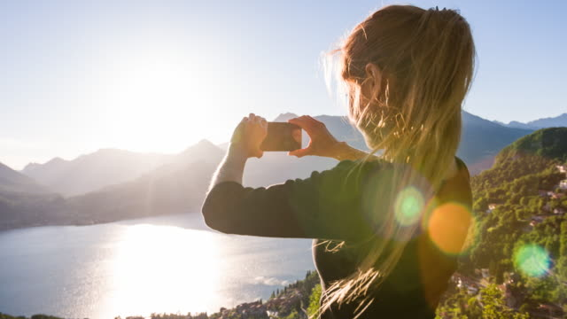 Woman taking pictures of lake at sunset