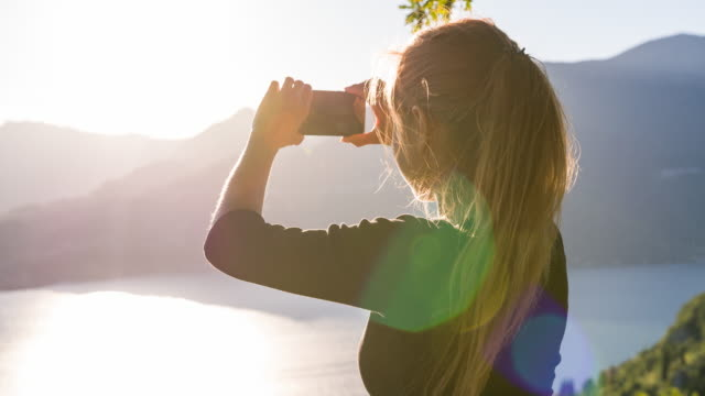 Woman taking pictures of mountain layers above lake at sunset