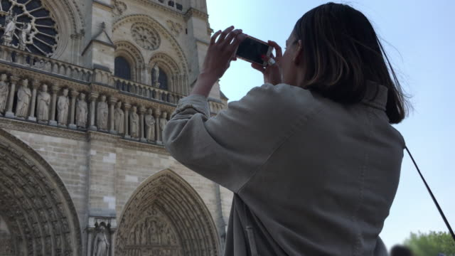 a woman taking pictures of notre dame cathedral traveling in paris, france, europe. - only mid adult women stock videos & royalty-free footage