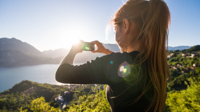 Woman taking pictures of panoramic view of lake and lakeside village