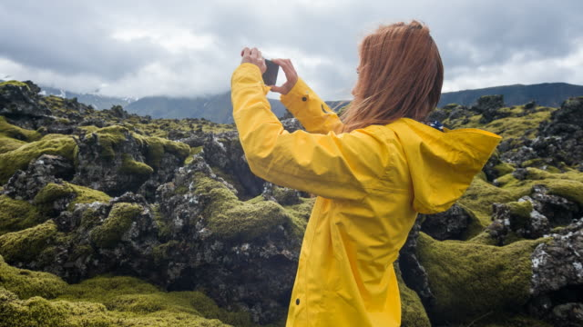 女性のスマート フォンでアイスランドの岩と苔の風景の写真を撮る - 地衣類点の映像素材/bロール