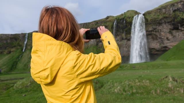kvinna att ta bilder av seljalandsfoss vattenfall - naturligt landmärke bildbanksvideor och videomaterial från bakom kulisserna