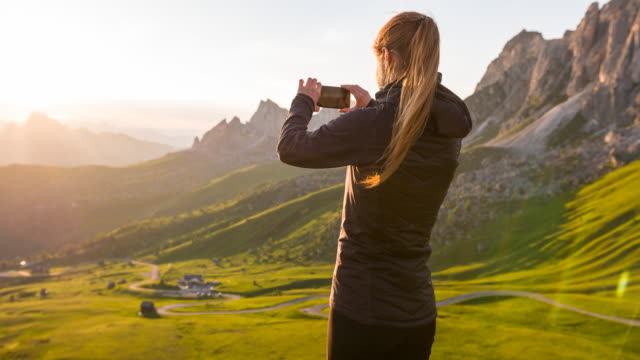 woman taking pictures of sunset in mountainside - photographing stock videos & royalty-free footage