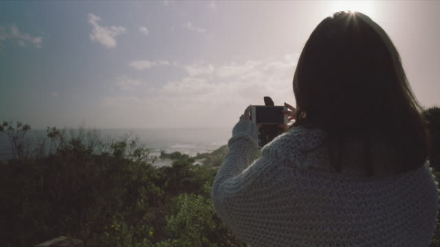 A woman taking pictures of the landscape and views, Mornington Peninsula, Victoria, Australia