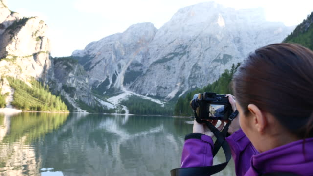 Woman taking pictures of the mountainside with camera