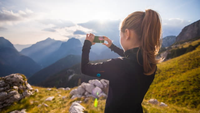woman taking pictures of the mountainside with smartphone - photographing stock videos and b-roll footage