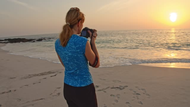 ws woman taking pictures on the beach at sunset - photographer stock videos & royalty-free footage