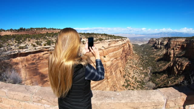 woman taking pictures using her smartphone, national park, usa - canyon stock-videos und b-roll-filmmaterial