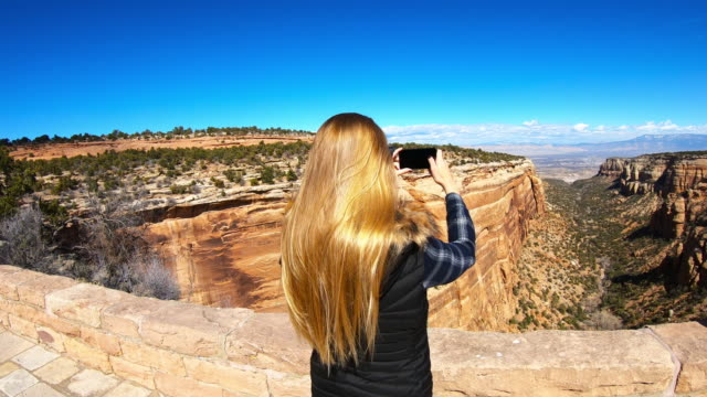vídeos de stock e filmes b-roll de woman taking pictures with her smartphone, canyon, national park - temas fotográficos
