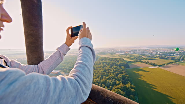 vídeos y material grabado en eventos de stock de slow motion mujer tomando fotos con el teléfono inteligente del globo de aire caliente - una mujer de mediana edad solamente