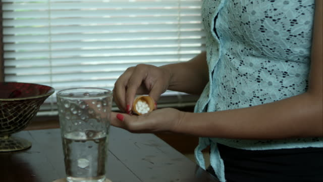woman taking pill with a glass of water. - taking medicine stock videos and b-roll footage