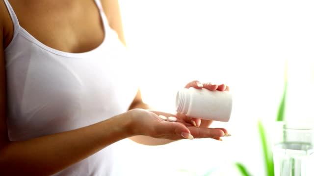 donna prendendo pillole. - attività che richiedono movimento video stock e b–roll
