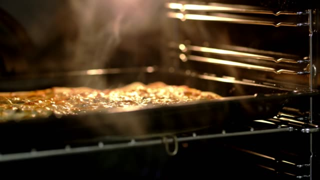 ds woman taking pizza out of the oven - stove stock videos & royalty-free footage
