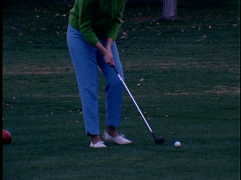1965 ms woman taking practice swing then driving golf ball from tee box / zo to ls woman picking up her tee + waving to camera - golf ball stock videos & royalty-free footage