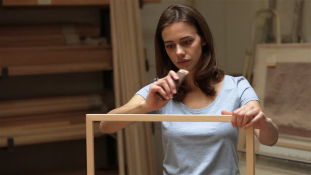 Woman taking pride in finished picture frame