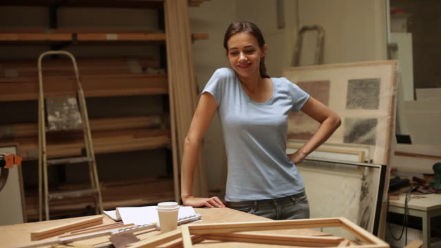 Woman taking pride in home-made picture frames